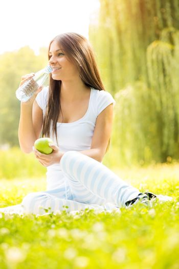 Smiling young woman holding an apple, drinks water from a bottle and enjoying in the nature.