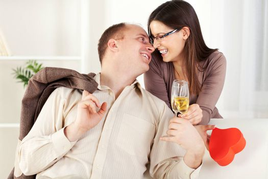 Happy Young couple in home interior enjoying in glass of champagne and touching noses. The valentine's day.