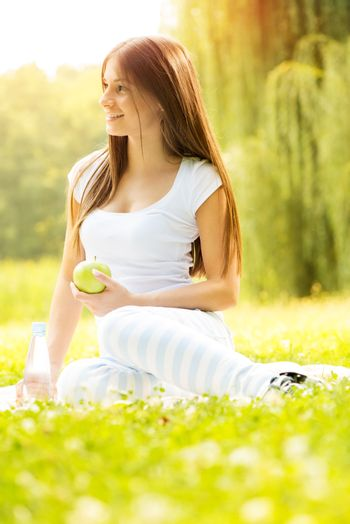 Smiling young woman holding an apple and enjoying in the nature.