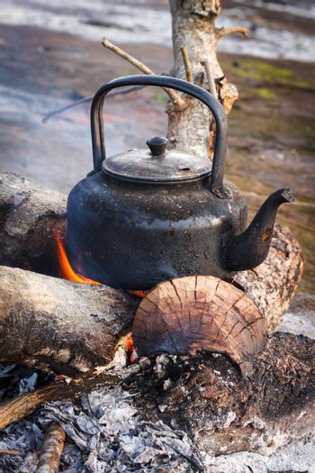 Old kettle  over the fire in camping.