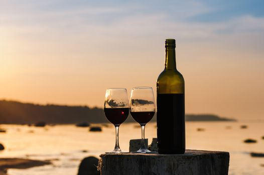 Red wine bottle and glasses on the shore in evening