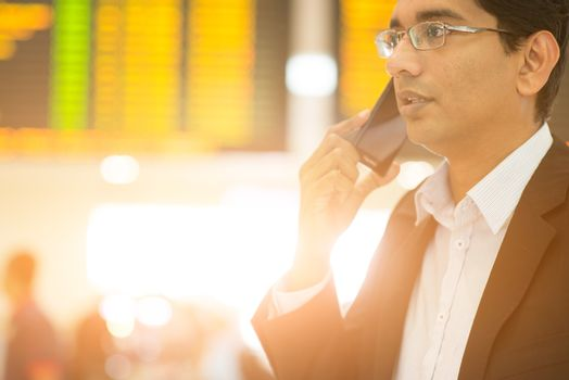 Asian Indian Business man on the phone during his business travel, at the airport, golden sun light background.