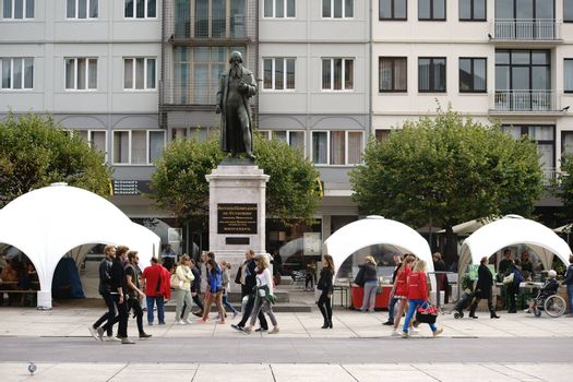 Mainz, Germany - September 25, 2015: Pedestrians crossing tents from a culinary market at the Gutenberg monument on the Gutenberg Square on September 25, 2015 in Mainz.