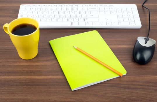 Keyboard with coffee and copybook