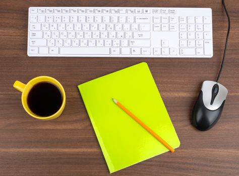 Keyboard with coffee and copybook on table