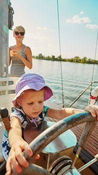 Little girl enjoying ride on yacht at sunset