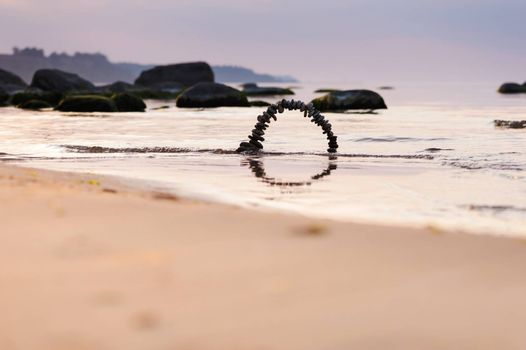 Arch of pebbles on the sandy beach of the sea