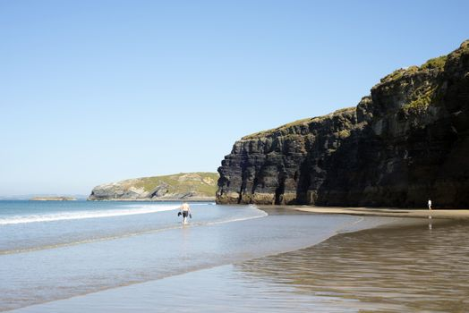 tourists in ballybunion beach and cliffs on the wild atlantic way at low tide