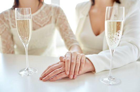 people, homosexuality, same-sex marriage, celebration and love concept - close up of happy married lesbian couple hands on top and champagne glasses