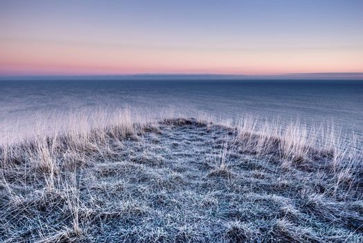 Panoramic view winter sea and frozen grass