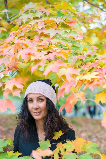 Beautiful woman in 40s captured by foliage tree