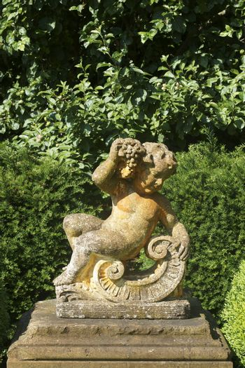 The sculpture of a little boy, Bacchus, made of concrete for garden decoration.