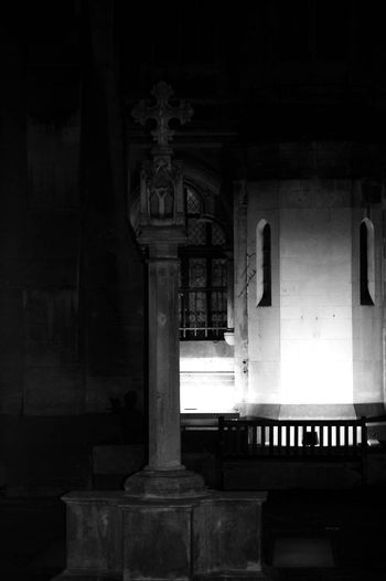 In the back yard of a church there is a cross in the dark night.