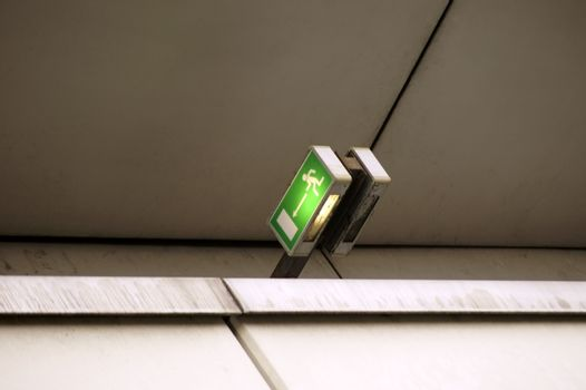 An illuminated emergency exit sign on an exit of a building.
