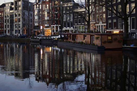Amsterdam, Netherlands - December 29, 2014: A canal or a side canal in Amsterdam with colorful houses reflected in the water in the early morning on December 29, 2014 in Amsterdam.