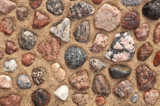 wet colourful stones arranged on sand as background