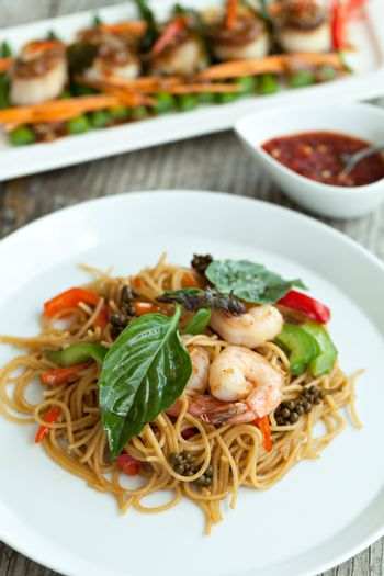 Thai food dishes with shrimp and noodles with scallops in the background. Shallow depth of field.