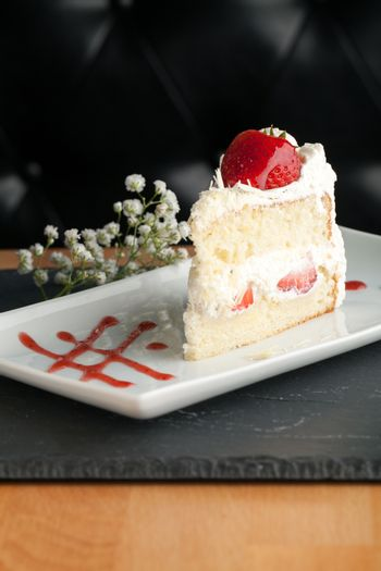 Slice of strawberry shortcake with white chocolate shavings.