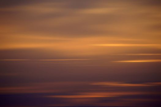 The photograph of a wiped orange and purple sunset.