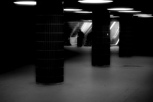 A dark underpass with round ceiling lights and an escalator.