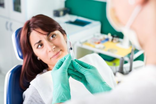 Young female dentist giving anesthesia to the patient before dental surgery. The patient in fear Expressing Negativity. Selective focus, focus on the patient.