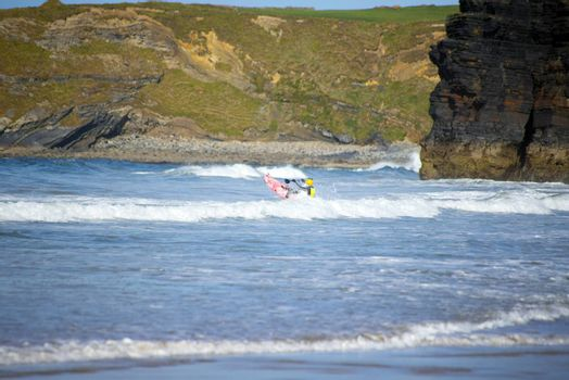 bright winter view of kayaker at ballybunion beach and cliffs on the wild atlantic way in ireland