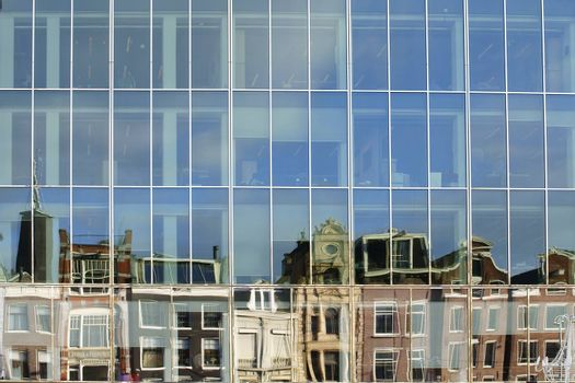 An abstract mirrored row of houses in the windows of a modern office building.