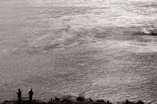 The silhouettes of two anglers standing in the evening light on a glittering river.
