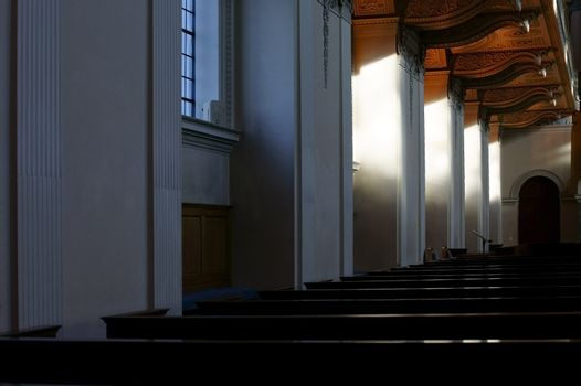 London, UK - November 29, 2014: Sunlight falls obliquely on the seats of the chapel of the Royal Naval College in Greenwich on November 29, 2014 in London.