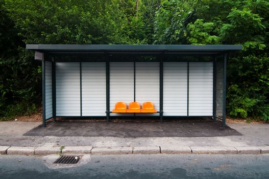 Bus station with orange plastic seats in the park