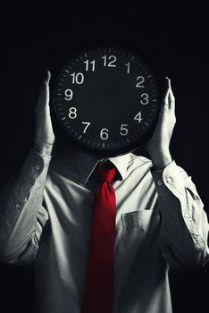 Businessman with black clock, deadline concept