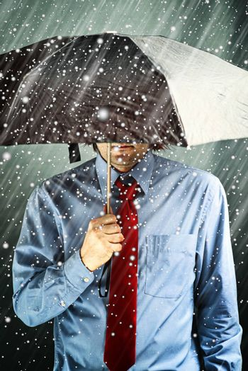 Businessman with black umbrella protecting himself from the storm. Financial problem, economic crisis, hard times concept.