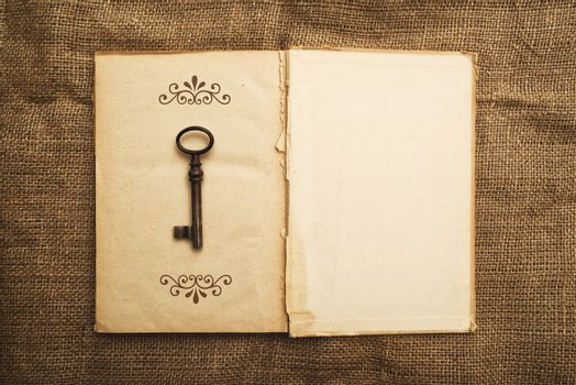 Old open book and rusty key
