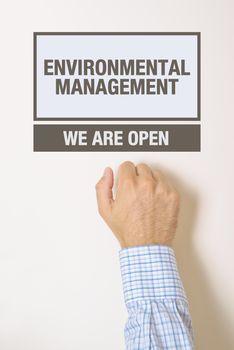 Businessman knocking on Environmental Management office door