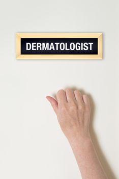 Female hand is knocking on Dermatologist door