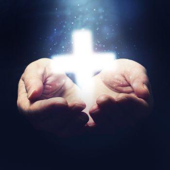 Open hands holding Christianity cross