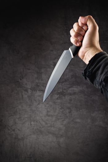 Hand with shiny knife, killer in action