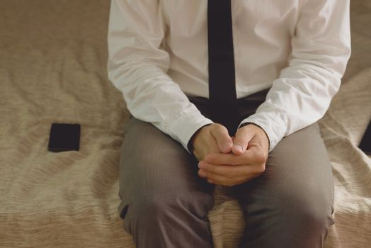 Lonely businessman in hotel room sitting on the bed
