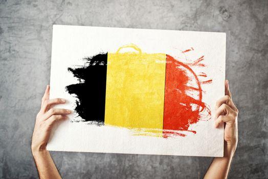 Belgium flag. Man holding banner with Belgium Flag.