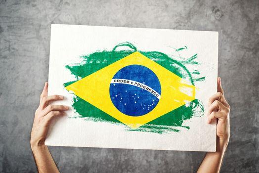 Brazil flag. Man holding banner with Brazilian Flag.
