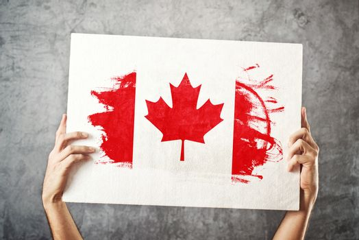 Canada flag. Man holding banner with Canadian Flag.