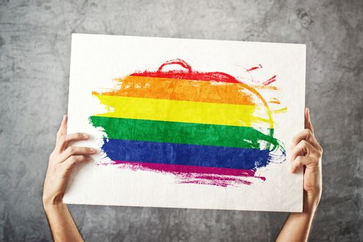 LGBT flag. Man holding banner with Gay Flag.