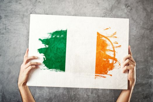 Ireland flag. Man holding banner with Irish Flag.