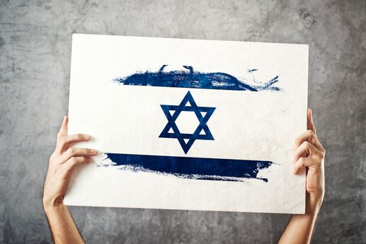 Israel flag. Man holding banner with Israelian Flag.
