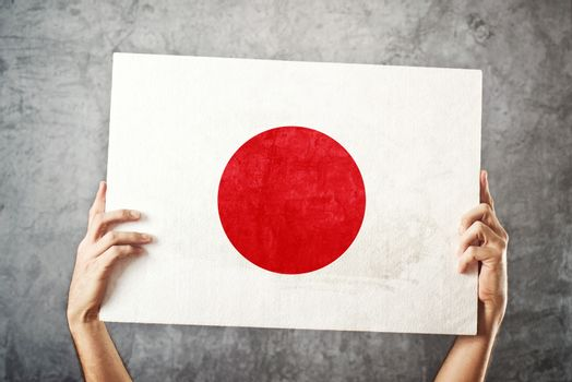 Japan flag. Man holding banner with Japanese Flag.