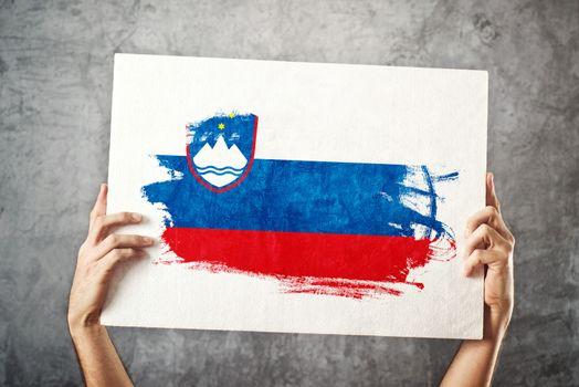 Slovenia flag. Man holding banner with Slovenian Flag.