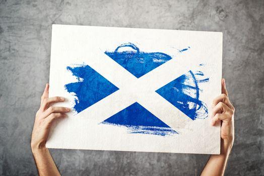 Scotland flag. Man holding banner with Scotish Flag.