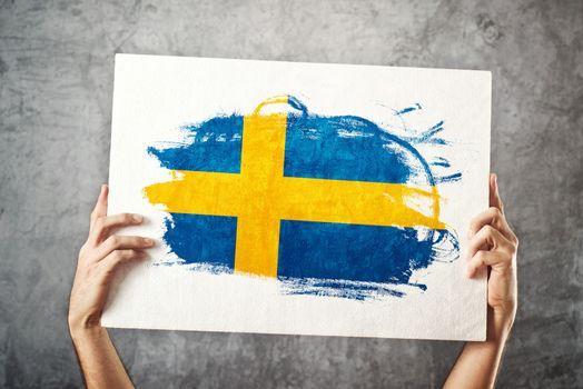 Sweden flag. Man holding banner with Swedish Flag.