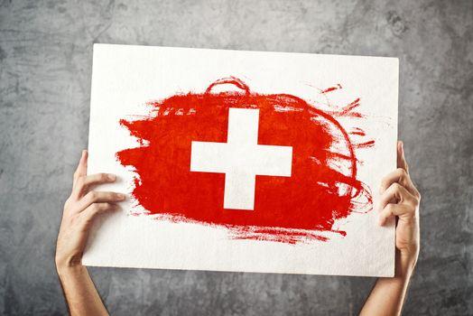 Switzerland flag. Man holding banner with Swiss Flag.