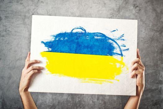 Ukraine flag. Man holding banner with Ukrainian Flag.